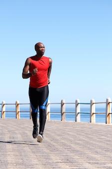 Fit african man jogging on seaside promenade