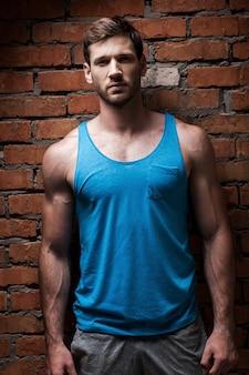 Подходит и уверенно. уверенный молодой мускулистый мужчина позирует, стоя у кирпичной стены