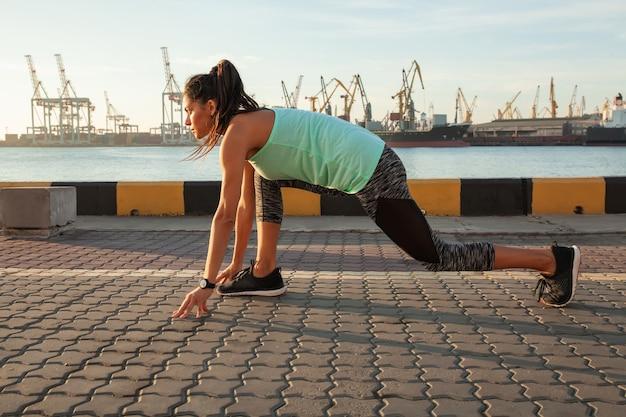달리기를 시작할 준비가 된 시작 위치에 있는 적합하고 자신감 있는 여성. 멀리 보고 스프린트를 시작하려고 하는 여성 운동선수.