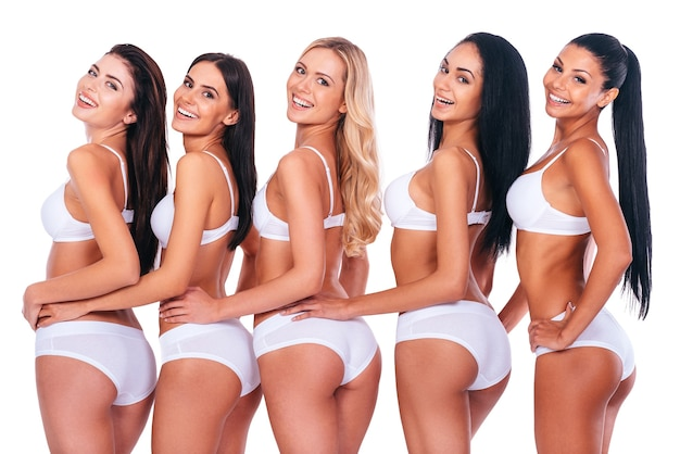 적합하고 매력적인. 란제리를 입은 아름다운 여성 그룹은 어깨 너머로 바라보고 서로에게 유대감을 주며 흰색 배경에 대해 줄지어 서 있는 동안 웃고 있습니다.