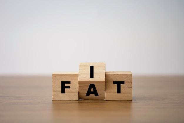 木製キューブブロックのフィットと脂肪の言い回し印刷画面。食事と健康状態。
