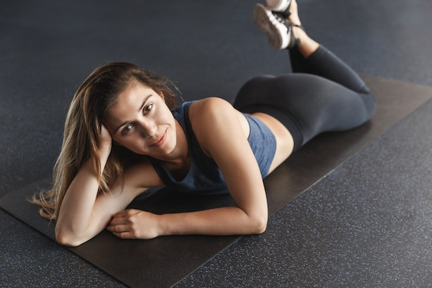 健康で健康的な若い女性の体型が良く、女性アスリートはゴム製のマットの上でリラックスして横たわっています。