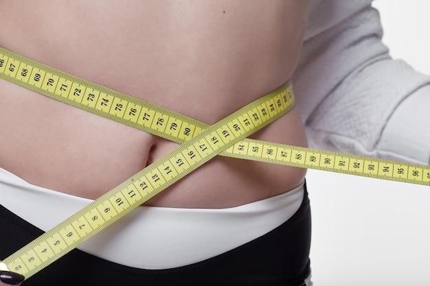 フィット感と健康な若い女性がセンチメートルとミリメートルの巻尺で腰を測定します。白の分離イメージ。