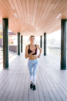 Fit and healthy young woman running at outdoors