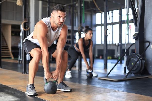 体育館でのエクササイズクラスでダンベルを持ち上げることに焦点を当てた、健康で筋肉質のカップル。