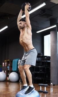 Подходящий и мускулистый мужчина упражнения с мячом на гимнастический мяч bosu полушария в тренажерном зале.