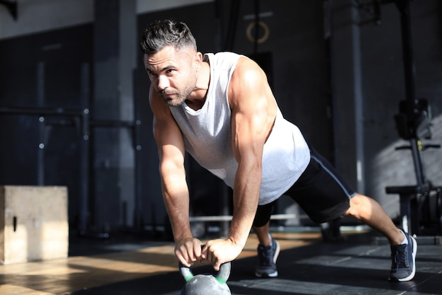体育館でのエクササイズクラスでダンベルを持ち上げることに焦点を当てた、健康で筋肉質の男性。