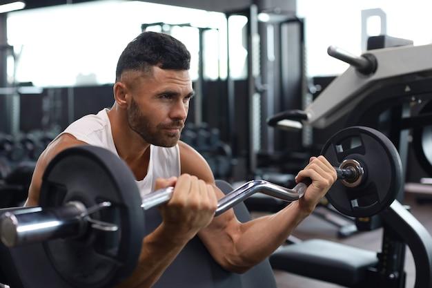 ジムのベンチを使用して重いバーベルの重量を持ち上げるフィット感と筋肉質の男。