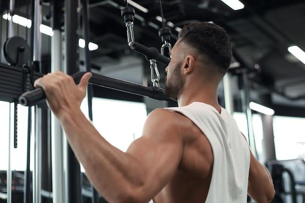 적합하고 근육질의 남자가 시뮬레이터에서 등을 흔듭니다. 뒷모습.