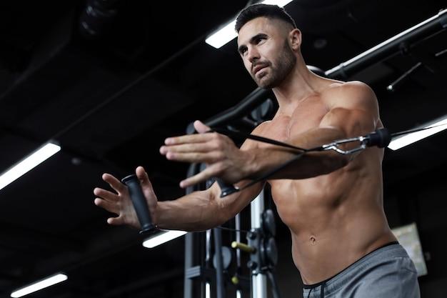 体にフィットして筋肉質の男性は、ジムのブロックシミュレーターで胸筋をトレーニングします。 Premium写真