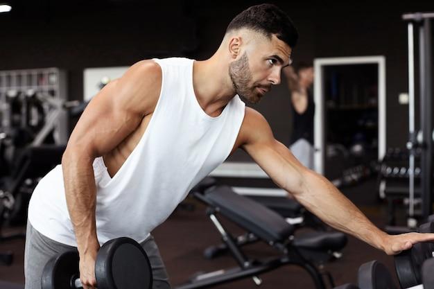 フィット感と筋肉質の男性がダンベルでトレーニングします。