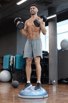 Подходящий и мускулистый мужчина, тренирующийся с гантелями на гимнастическом мяче bosu полушария в спортзале.
