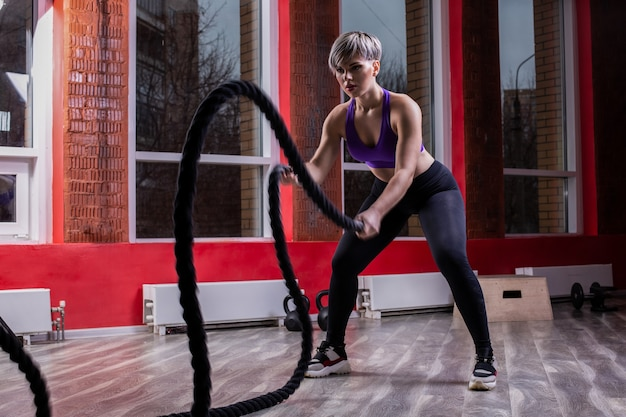 피트니스 스튜디오에서 로프와 싸우는 운동 적합하고 근육질의 여성