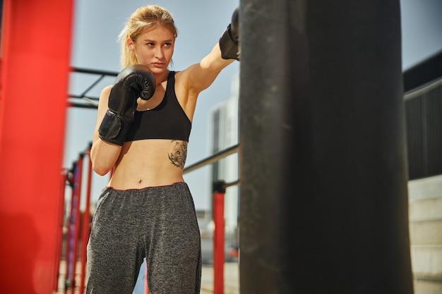 フィット感とスポーティな女性は、スポーツグラウンドでのkikcboxingトレーニング中に左ボクシンググローブでパンチしています