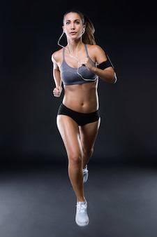 Fit and sporty young woman running over black background.