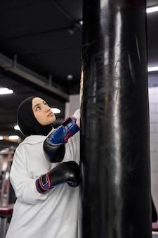 ハードボクシングのトレーニングの後に休憩を取っているアラビアの女性に合う、イスラム教徒の女性はジムで、カメラでポーズをとっているサンドバッグの近くに立っています。ヒジャーブの女性