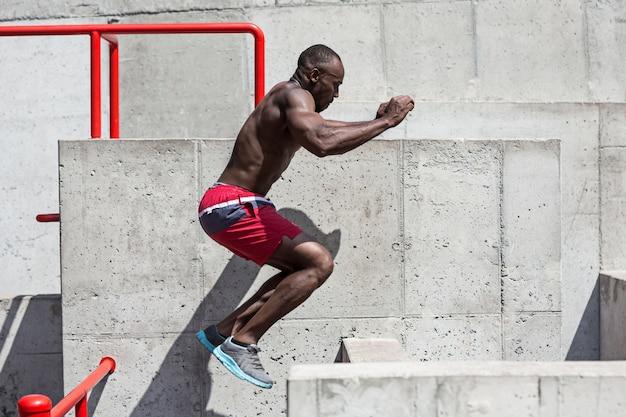 Подходит спортсмен, делая упражнения на стадионе. афро-мужчина на открытом воздухе в городе. прыжковые спортивные упражнения. фитнес, здоровье, концепция образа жизни