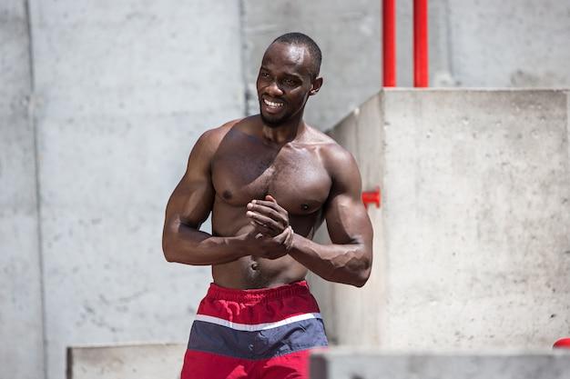 Подходит спортсмен, делая упражнения на стадионе. афро-мужчина на открытом воздухе в городе. подтягивание спортивных упражнений. фитнес, здоровье, концепция образа жизни