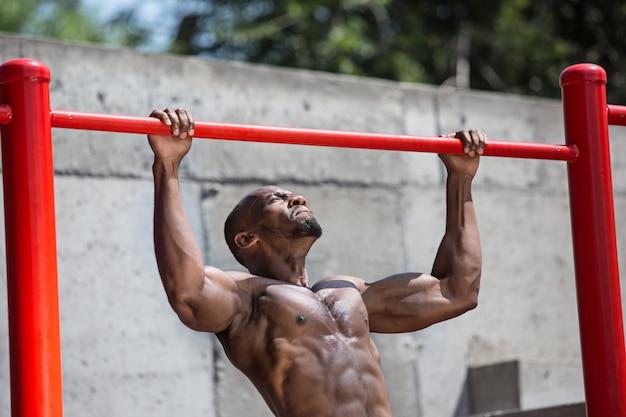 Подходит спортсмен, делая упражнения на стадионе. афро-мужчина на открытом воздухе в городе.