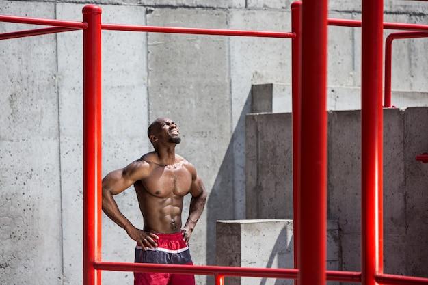 L'atleta in forma facendo esercizi allo stadio. uomo afro o afroamericano all'aperto in città. tirare su esercizi sportivi. fitness, salute, concetto di stile di vita