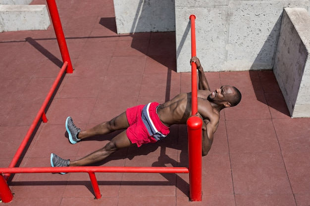 The fit athlete doing exercises at stadium. afro or african american man outdoor at city. pull up sport exercises. fitness, health, lifestyle concept