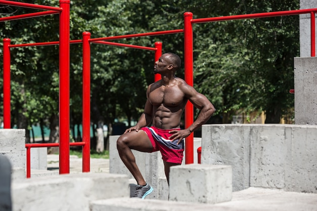 Fit athlete doing exercises at stadium. afro or african american man outdoor at city