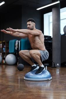 Подходящий спортсмен, выполняющий упражнение на гимнастическом мяче босу полушария в тренажерном зале.