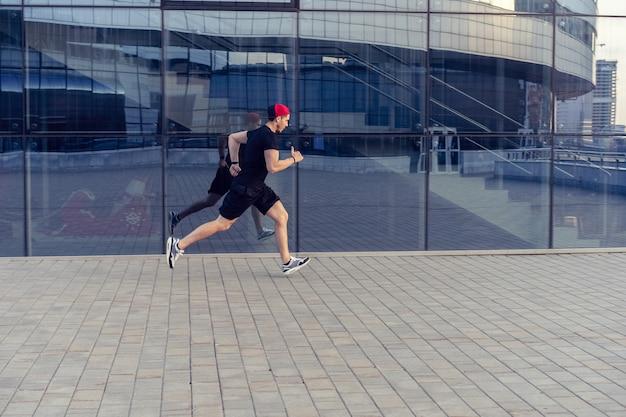 健康を維持するために屋外で走っているアスリートにフィットします。走るスポーティな青年