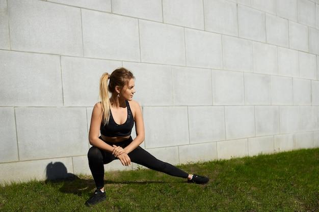 화창한 여름 날에 잔디에 측면 돌진을하고 야외에서 운동하는 세련된 검은 색 스포츠 옷을 입고 포니 테일을 입고 운동 금발 소녀를 맞추십시오. 사람, 활동, 에너지, 유연성 및 지구력