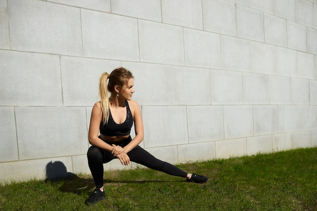 Fit athletic blonde girl wearing ponytail and stylish black sports outfit exercising outdoors, doing side lunges on grass on sunny summer day. people, activity, energy, flexibility and endurance