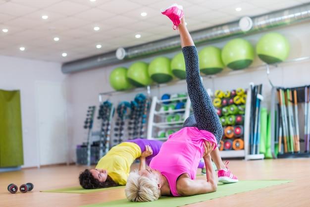 밝은 스포츠 장비에 대해 체육관에서 그룹 수업에서 매트에 단일 다리 브리지 운동을하는 운동 여성에 적합