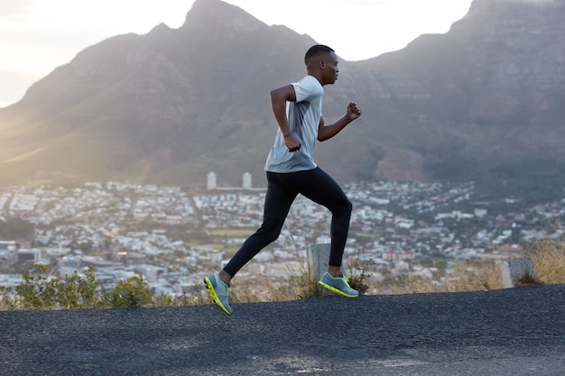 Fit athletic male jogger runs fast along road, does workout outdoor, amazing mountain landscape, breathes fresh air, dressed in casual clothes for sport. people and recreation concept