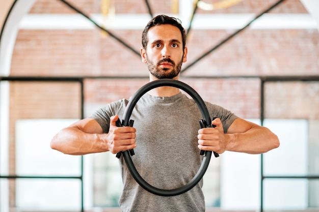 필라테스 매직 서클 또는 링을 사용하여 근육을 강화하고 체육관에서 자세를 가까운 상체 보기에서 정렬하기 위해 운동하는 남자에게 적합합니다.