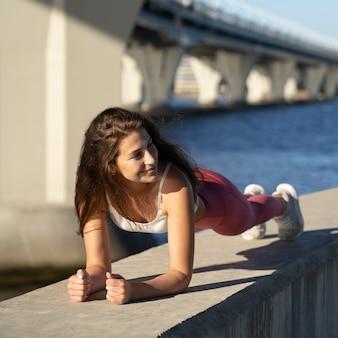 板の運動、堤防でのクロスフィットトレーニングを行う運動女性にフィット