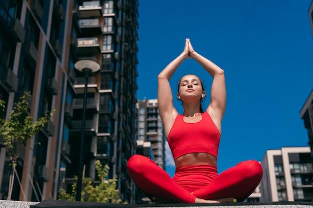 階段で上向きの敬礼でヨガの蓮の瞑想の位置に運動の女性をフィットさせます