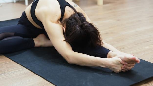 Montare la giovane donna atletica facendo stretching yoga in soggiorno.