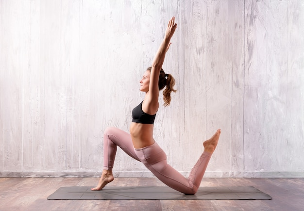 Fit attractive muscular young blond woman doing a low lunge variation yoga pose on a mat
