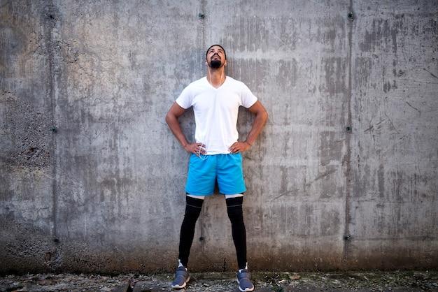 Sportivi in forma e attraenti contro il fondo del muro di cemento che ascolta la musica e che osserva in su