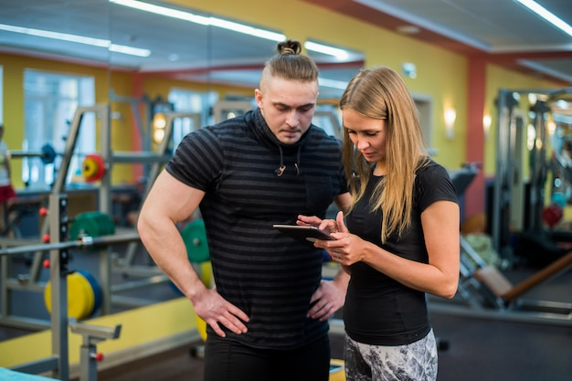 Приспособьте привлекательную молодую пару в спортзале, смотрящем на планшетный пк, поскольку они следят за своим прогрессом и фитнесом