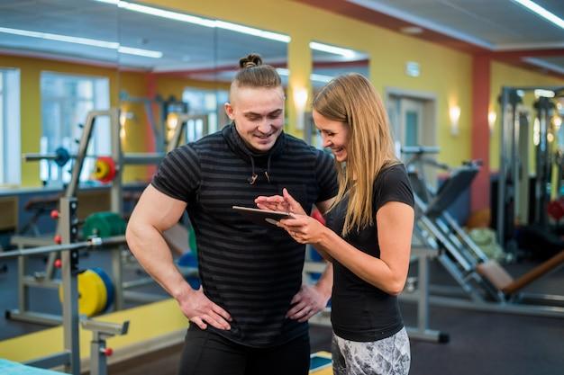 タブレットpcを見て、進捗状況とフィットネスを監視しているジムで魅力的な若いカップルに合う
