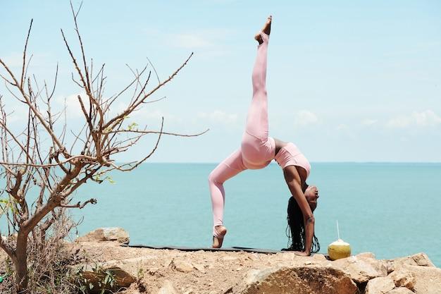 Подходящая привлекательная молодая женщина делает позу моста на одной ноге на горе с красивым морем в фоновом режиме
