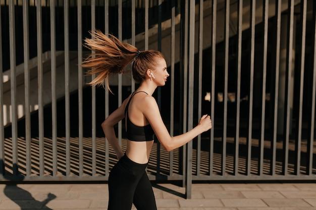 Подходит привлекательная молодая женщина, упражнения на открытом воздухе. здоровая молодая спортсменка делает фитнес-тренировку в солнечный теплый день.