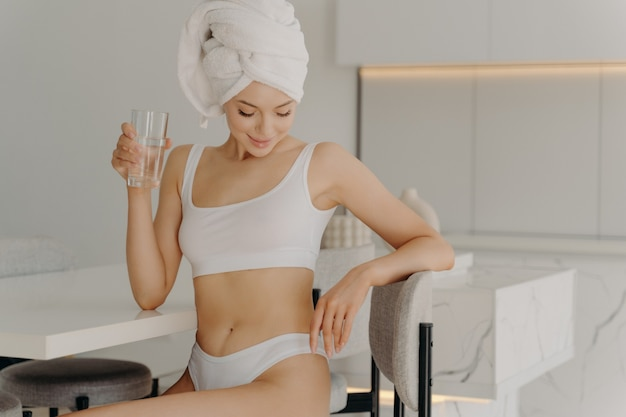 물 한 잔을 마시는 동안 부엌에 앉아 있는 매력적인 젊은 여성, 일상적인 샤워 절차 후에 수분을 보충하고 속옷과 수건을 머리에 감습니다. 건강한 아침 습관