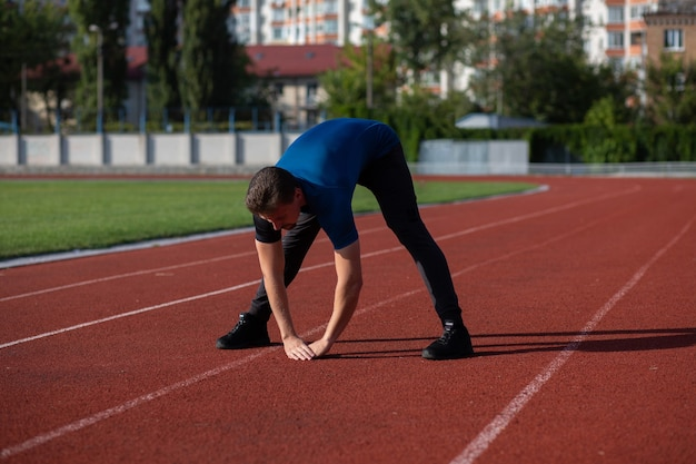 Fit bearded man warms up before workout at the staduim. space for text
