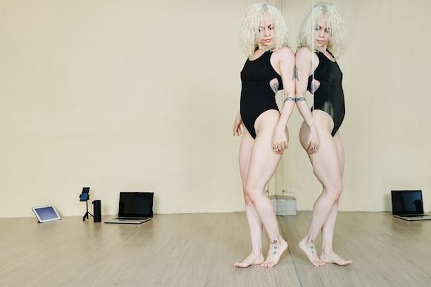 큰 댄스 클래스 거울에서 그녀의 몸을보고 즐기는 아름다운 댄서 맞추기