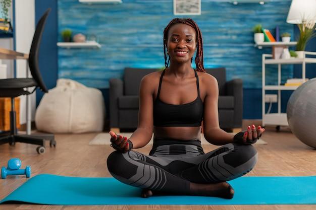 スポーツのトップで足を組んで、蓮華座にレギンスを着て座ってヨガを練習している黒人女性にフィットします。家庭の居間でストレスのない生活を送るために、落ち着いた心の調和を実践します。