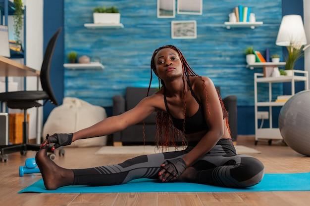 ダンベルトレーニングで自宅で激しいトレーニングをした後、ヨガマットの上に座ってつま先までストレッチする黒人女性にフィットします。健康的なライフスタイルの幸福のために筋肉をリラックスさせます。