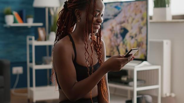 운동복을 입은 흑인 여성이 거실에서 아침 운동을 하는 동안 전화로 피트니스 온라인 교육을 검색하는 요가 스위스 공에 앉아 있습니다. 건강한 라이프 스타일을 즐기는 슬림 애슬리트 성인