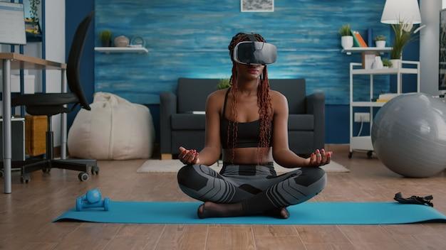 Donna di colore in forma che indossa le cuffie per la realtà virtuale mentre è seduta sulla mappa dello yoga