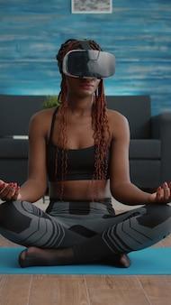Donna di colore in forma che indossa le cuffie per realtà virtuale mentre è seduta sulla mappa dello yoga